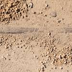 image: a rail just about visible in sandy soil