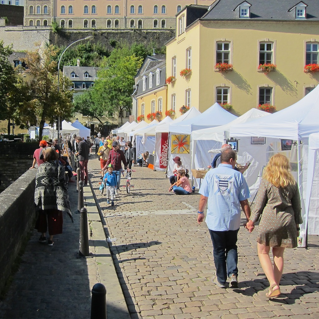 image: lots of gazebos sitting in a row on a cobblestone bridge under the september sun